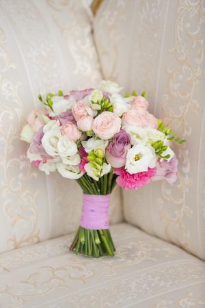 ramo de novia de color rosa suave en un sofá de color beige