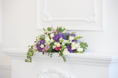 Elegante chimenea blanca llena de flores en lugar de fuego. Habitación elegante Foto de archivo