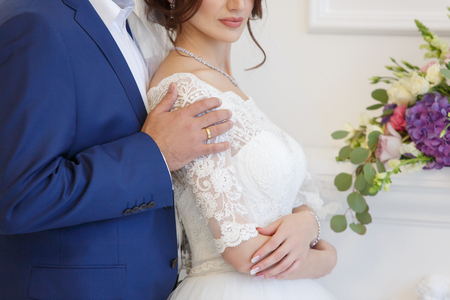 Chic wedding couple groom and bride in an embrace in a white Studio.