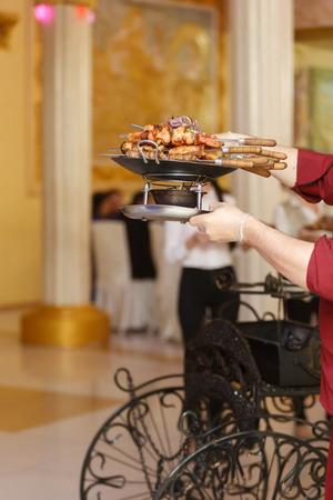Placa de shish kebab cocinado en pinchos.