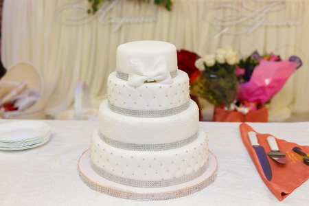 white wedding cake decorated with a bow from mastic Foto de archivo