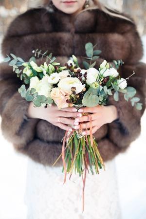 Boda del invierno. La novia tiene en la mano el ramo de rosas y algodón.