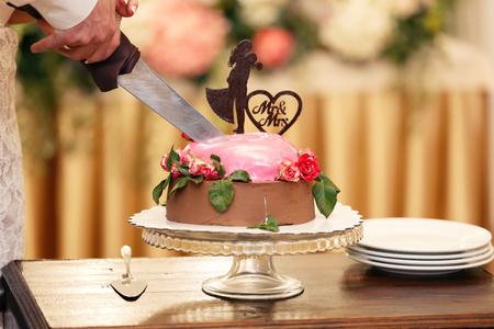 Newlyweds cutting the chocolate wedding cake for the newlywed Foto de archivo