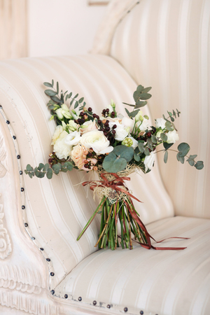 gentle bridal bouquet from roses and greenery with a brown tape. Rustic style.
