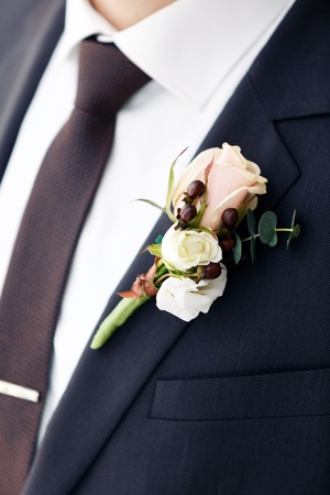 graceful stylish buttonhole of the groom from a rose and berries