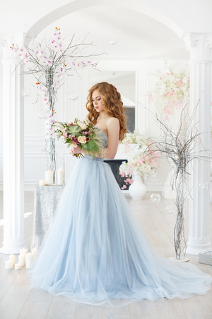 Novia en un interior de luz en azul vestido de novia con un ramo de manos en una mañana sobre la decoración creativa fantástica