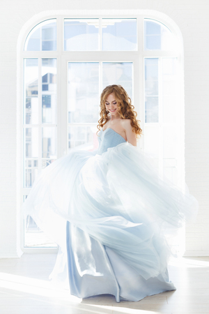 the beautiful bride in a blue dress to be turned against a light window. Light photo, white interior Foto de archivo