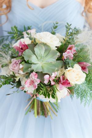 La niña en un vestido azul de pie sobre un fondo de madera gris y tiene un hermoso ramo de flores suculentas, blanco, rosa y verde
