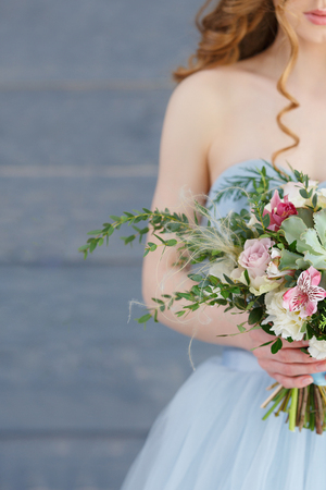 The girl in a blue dress standing on a gray wooden background and holds a beautiful bouquet of succulents, white, pink flowers and greenery