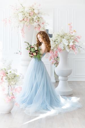 Novia en un interior de luz en azul vestido de novia con una mañana sobre la decoración creativa fantástica