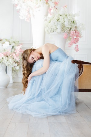 bride in a light interior in blue wedding dress with in a morning over fantastic creative decoration