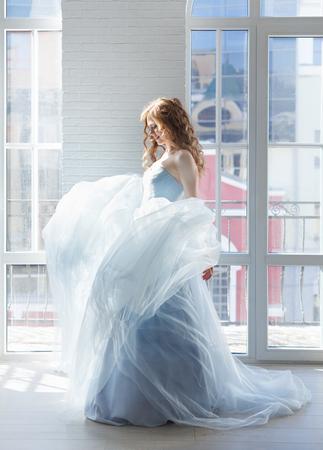 La novia hermosa en un vestido azul para ser dado vuelta contra una ventana ligera. Foto ligera, interior blanco Foto de archivo