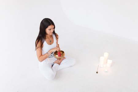 girl the yogi plays on the Tibetan singing bowl. Yoga and healthy lifestyle concept. Girl the yogi wearing sportswear white suit, full length, white studio