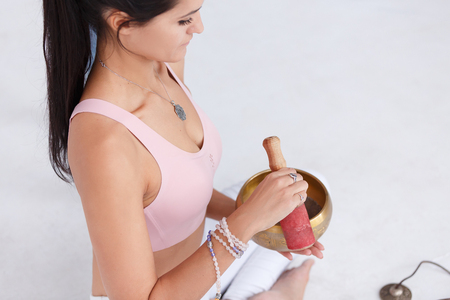 girl the yogi plays on the Tibetan singing bowl. Young woman meditating in a yoga on white background, Yoga and healthy lifestyle concept Stock Photo