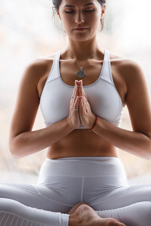 Lotus pose, yoga hands close up. Yoga woman in white sport clothes meditation. Young woman relax and exercising in white class yoga against window. Freedom