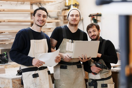 Master of small business with laptop and his team as sign of innovation in carpenter workshop. startup business, young specialist Stock Photo