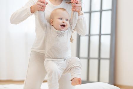 귀여운 작은 아기 걸어서 학습하는 동안 웃 고, 엄마는 그의 손을 잡고있다. 아이의 첫 단계. 백색 가벼운 국내 인테리어, 흰색 옷 스톡 콘텐츠