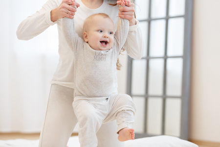 Cute little baby is smiling while learning to walk, mom is holding his hands. first steps of child. White light domestic interior, white clothes