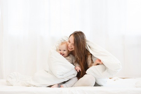 happy young mother having fun with the little baby boy under a blanket in a light bedroom before bedtime. Family wearing in white pajamas