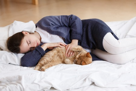 young girl in a blue pajamas sleeps on a big white bed with a red cat. Healthy day sleep. Top view Archivio Fotografico
