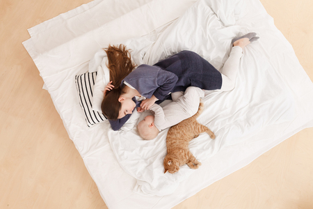 young caucasian mother sleeps together with baby boy in the afternoon in a bed together with a red cat. Focus on woman, top view. Healthy day sleep. Standard-Bild
