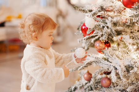 horizontal portrait of child 1 years old stands near New Year tree, holds decorated new year ball, decorates fir tree, has happy expression, anticipates miracle. Family, Christmas, holiday, children Banco de Imagens - 91320766