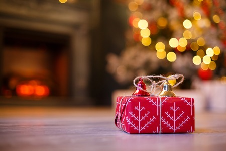 Gift boxes with gold and red Jingle Bells against a bokeh of twinkling party lights. Luxury New Year gift. Christmas gift. Christmas with gift box. Christmastime celebration Stock Photo