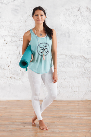 Full-growth portrait of beautiful young brunette woman in top and leggings holding blue mat for practicing yoga in sport hall
