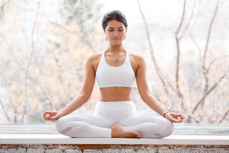 ?harming young woman sitting in lotus pose and meditating with closed eyes during yoga classes on the windowsill in the gym
