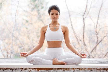 blesser une jeune femme assise en posture de lotus et méditer les yeux fermés pendant les cours de yoga sur le rebord de la fenêtre du gymnase Banque d'images