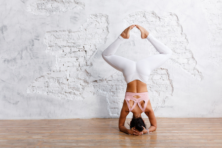 Unidentified beautiful young woman makes stand on her head with legs apart - an exercise of yoga - in an empty gym on white wall background