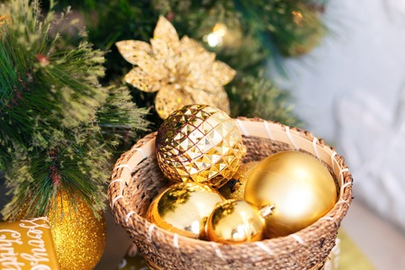 Close up of a Christmas tree and decoration with gold ball on white brick wall background.