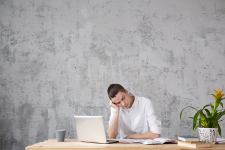 Tired cute young businessman looking through reports sitting at table with laptop on gray wall background. Thoughtful manager or freelancer generates new ideas. Copyspace Banco de Imagens - 98730045