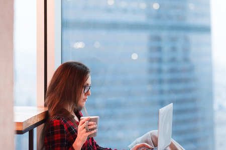 Portrait of cute young female manager in casual clothes and glasses working with laptop and cup of coffee near large window overlooking the skyscrapers