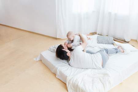 top view-Family weekend together, lazy shining morning, cozy and warm photo. Playful parents and their infant in white pajamas in sunny bedroom Mom and dad making kid smiling. Copyspace