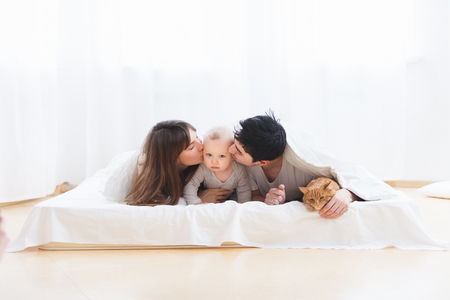 Concept of happy young family. Unidentified young parents kiss small one-year-old charming child lying on bed with red cat. Funny white scene