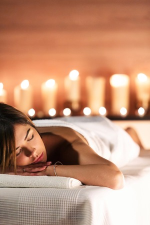 Spa concept. Beautiful young woman lies on massage table and relax on background of blurry candles. Beauty, spa, healthy lifestyle