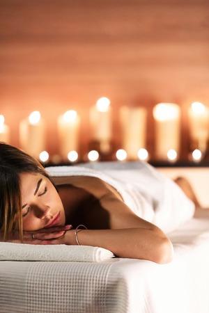 Spa-Konzept. Schöne junge Frau liegt auf Massagetabelle und entspannt sich auf Hintergrund von undeutlichen Kerzen. Schönheit, Wellness, gesunder Lebensstil Standard-Bild