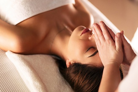 Concert of the spa. Hands of unidentified female masseuse doing massage on face of beautiful young girl lying on massage table in spa salon. Beauty, spa, healthy lifestyle