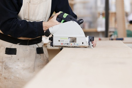 close-up of a circular saw in the hands of a man on a wooden desktop. Craftsman makes own successful small business. Craftsman makes own successful small business.