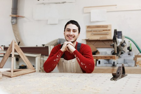 Portrait of a worker in work clothes in front of workbench tools  Portrait of man at work in workshop in garage at home. Place for the text.