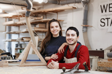 young happy family standing at a work bench in a carpentry workshop, writing a project. Family business. startup business. young specialist designer.