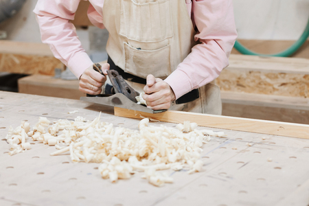 close-up of a male worker in a carpentry shop holds a plane in the hands. on a table of wood are sawdust. joiners workshop.