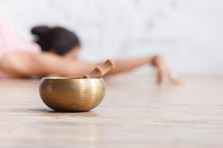 Bronze Tibetan singing bowl and pestle on the background of blurred young unidentified woman doing yoga exercises in an empty gym