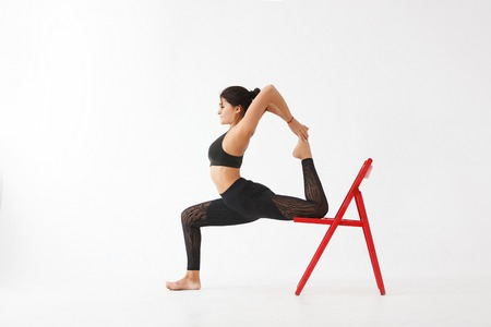 Beautiful young female yoga instructor in black gymnastic costume on red chair.