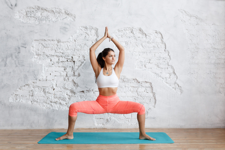 Portrait of young attractive yogi woman practicing yoga concept, standing in Sumo Squat exercise, Goddess pose, working out, wearing sportswear bra and pants, full length, white loft studio, white brick wall background Banque d'images