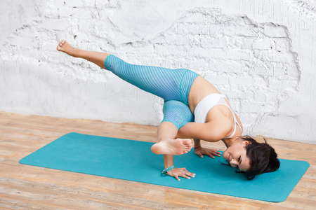 Young beautiful caucasian woman in yoga pose in studio on white brick wall background. Healthy life yoga concept. working out, wearing sportswear, white shirt, green pants
