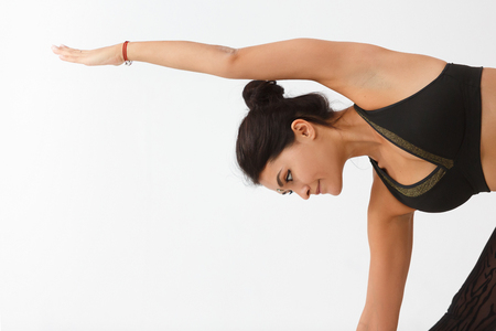 Sporty beautiful young woman practicing yoga, doing Revolved Triangle Pose, Parivrrta Trikonasana, working out wearing black sportswear, white studio, full length, white background
