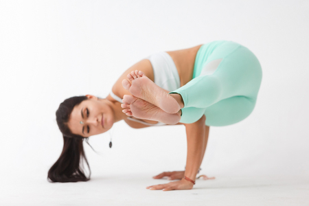 Close-up of blurred young female yoga instructor doing  difficult exercise lifting both feet on white isolated background Stockfoto