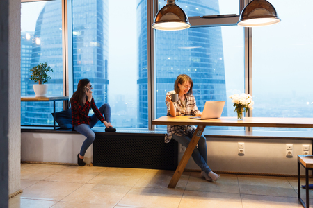 Creative studio for freelancers. Two young charming girls copywriter and freelancer working with computer and smartphone sitting in office on background of large window with view of business center